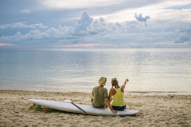 Glückliches paar mit paddelbrett am strand bei sonnenuntergang