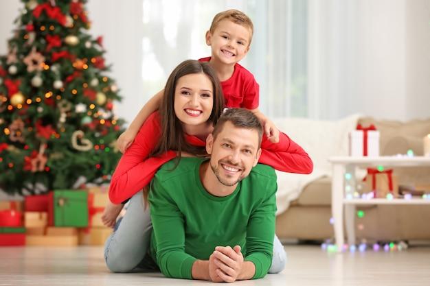 Glückliches paar mit sohn im weihnachtlich dekorierten wohnzimmer