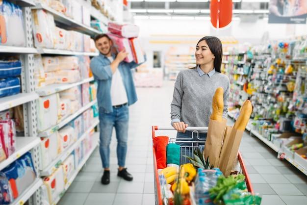 Glückliches paar mit wagen, der viele windeln in einem supermarkt kauft, familieneinkauf. kunden im geschäft, käufer auf dem markt, warenabteilung für kinder