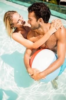 Glückliches paar mit wasserball im pool