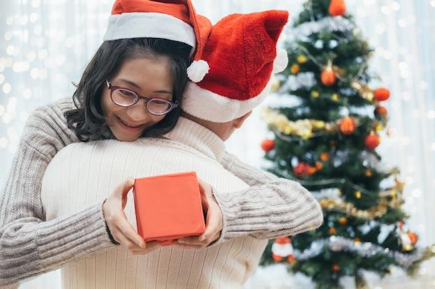 Glückliches paar mit weihnachtsgeschenk sitzen und umarmen.