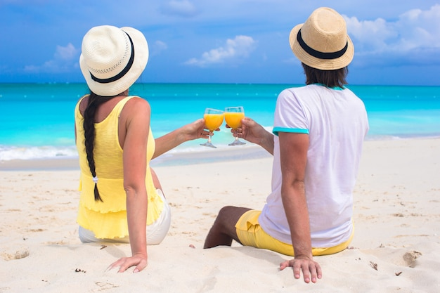 Glückliches paar mit zwei gläsern orangensaft auf strandferien
