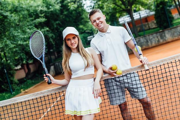Glückliches paar, nachdem tennis auf gericht gespielt worden ist. porträt des lächelnden jungen mannes und der schönheit mit tennisschlägern.