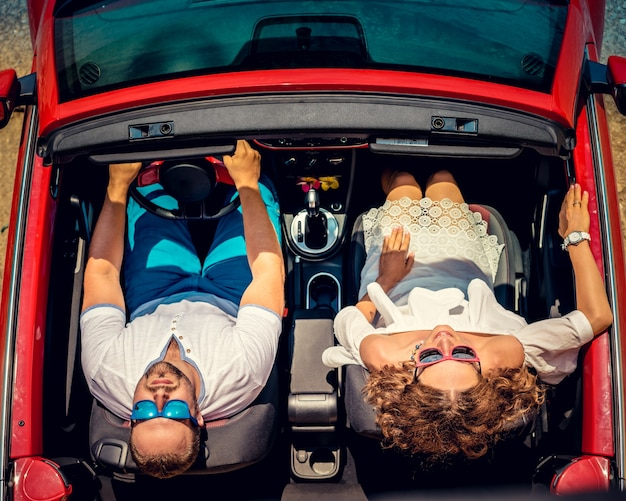 Glückliches paar reisen mit dem auto frau und mann haben spaß im roten cabrio sommerurlaub und reisekonzept draufsicht travel