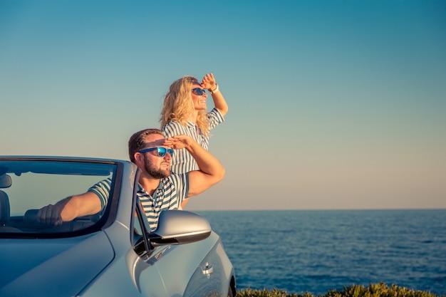 Glückliches paar reisen mit dem auto leute, die spaß im blauen cabriolet sommerferienkonzept haben