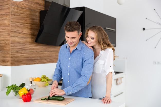 Glückliches paar schneidet gemüse für salat und flirtet in der küche