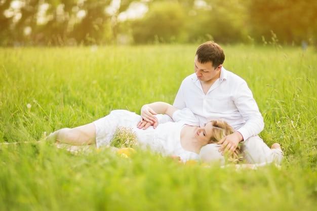 Glückliches paar - schwangere frau und ihr mann sitzen auf dem rasen im park.
