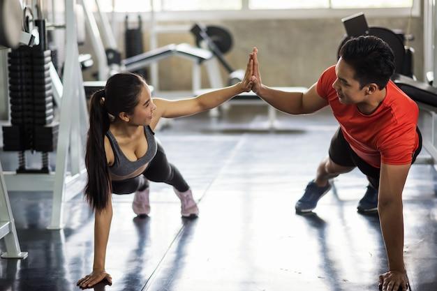 Glückliches paar sitzen im fitnessstudio