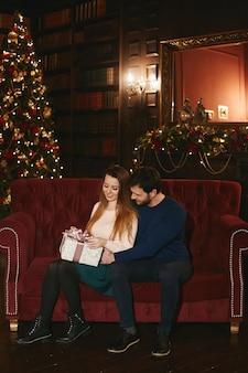 Glückliches paar sitzt auf der roten couch, schöner mann, der vorbildliche frau umarmt, die weihnachtsgeschenkbox hält