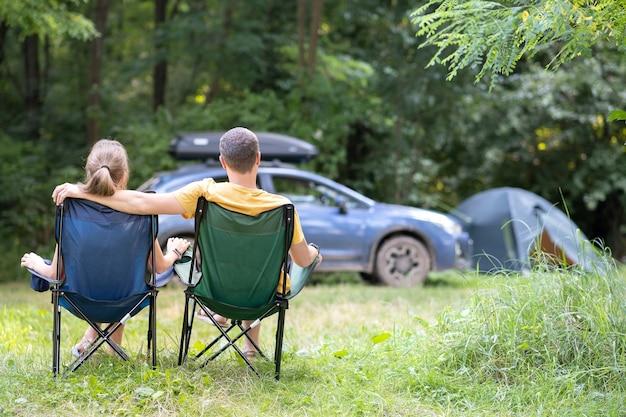 Glückliches paar sitzt auf stühlen auf dem campingplatz und umarmt sich zusammen. reise-, camping- und urlaubskonzept.