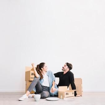 Glückliches paar sitzt vor umzugskartons