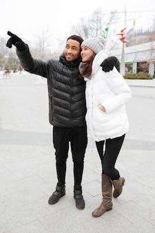 Glückliches paar stehend und wegweisend auf winterpark