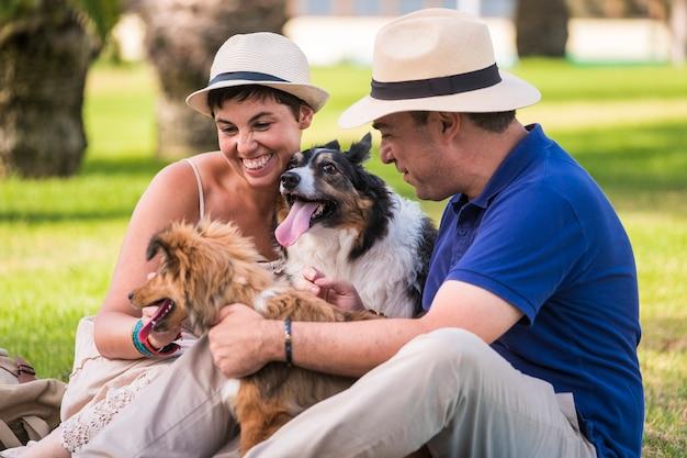 Glückliches paar tierhundeliebhaber genießen die freizeitaktivität zusammen im outdoor-park, lächeln und haben spaß mit ihren zwei entzückenden lieben haustieren - kaukasier haben spaß
