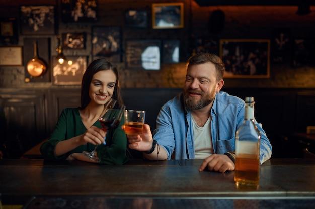 Glückliches paar trinkt alkohol an der theke in der bar