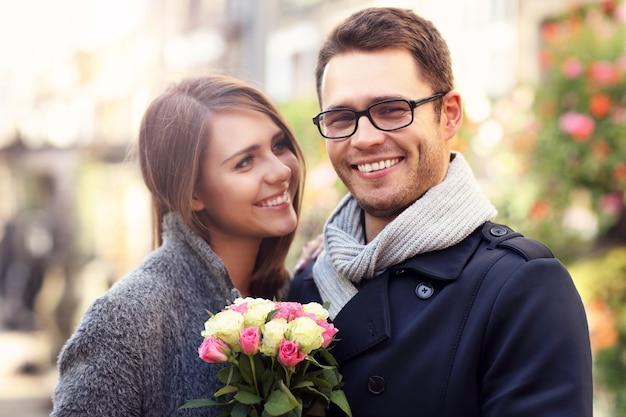 Glückliches paar umarmt mit blumen in der stadt