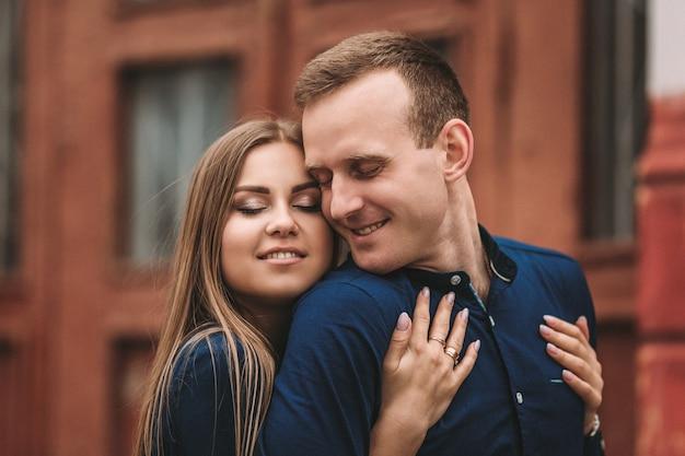 Glückliches paar umarmt und lächelt. porträt eines mannes und eines mädchens mit einem lächeln auf den gesichtern.