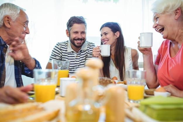 Glückliches paar und eltern unterhalten sich beim frühstück