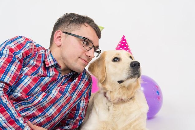 Glückliches paar und ihr hund feiern ein jahr geburtstag