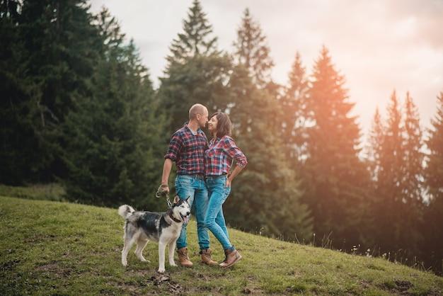 Glückliches paar verliebt in husky-hund, der spaß in den sommerferien hat.