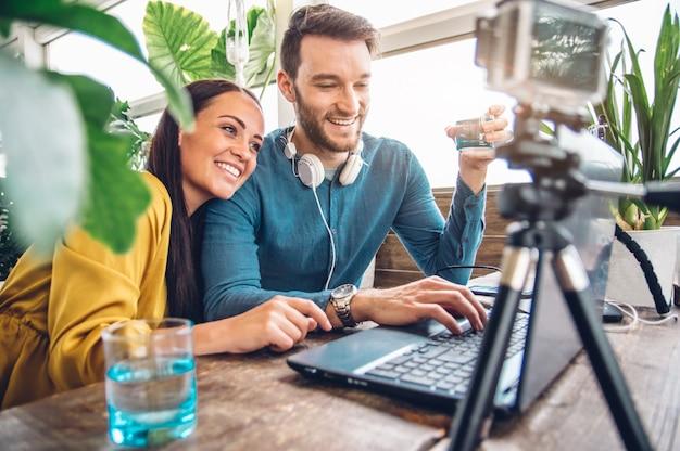 Glückliches paar von bloggern, die ein video aufnehmen, das sich auf das posten in sozialen netzwerken vorbereitet
