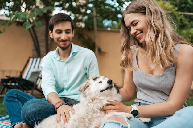Glückliches paar von jungs, die mit ihrem hund im hinterhof auf dem rasen spielen. fröhlicher alter hund