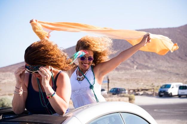 Glückliches paar von schönen freien unabhängigen fröhlichen menschen frauen im freien aus dem cabrio auto spielen mit dem wind in einem reise-drive-konzept für urlaub sommerferien