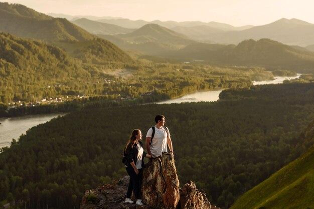 Glückliches paar von touristen mann und frau mit rucksäcken gewinner des berggipfels.