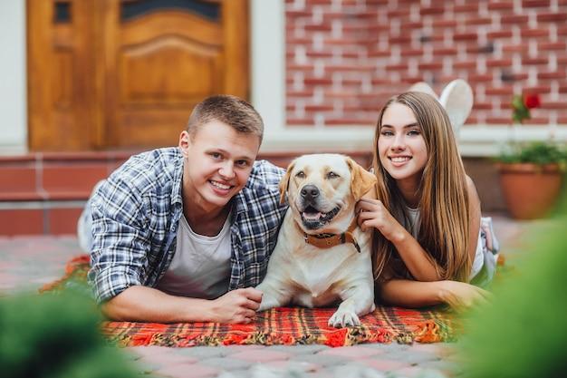 Glückliches paar von zwei ruht sich mit einem hund im innenhof aus