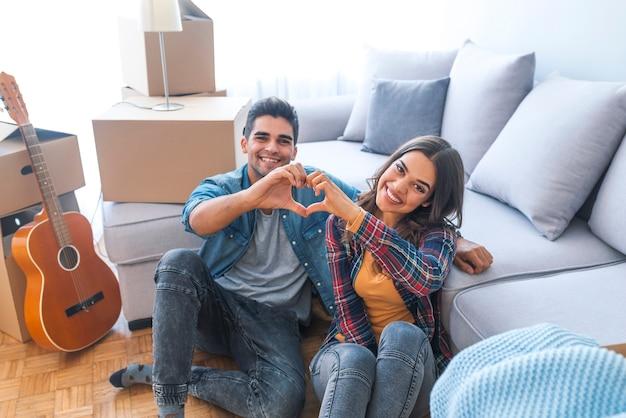 Glückliches paar während des beweglichen hauses, das herzzeichen zeigt