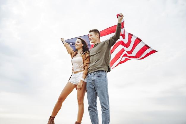 Glückliches paar, welches die amerikanische flagge in der natur hält