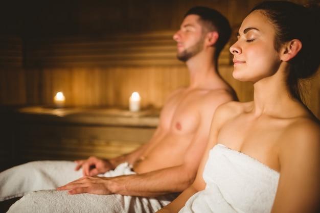 Glückliches paar, welches zusammen die sauna genießt