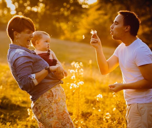 Glückliches paar wirft mit ihrem kleinen kind in den strahlen der goldenen sonne auf