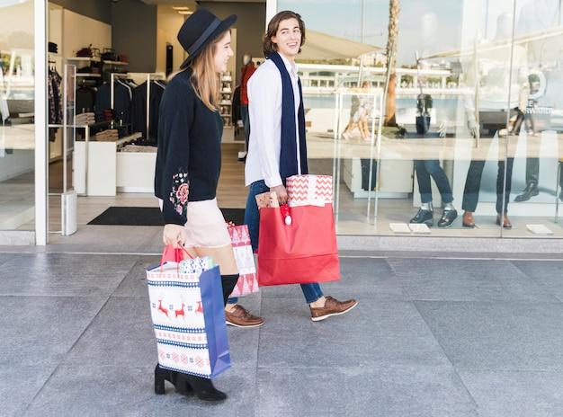 Glückliches paar zu fuß mit einkaufstüten