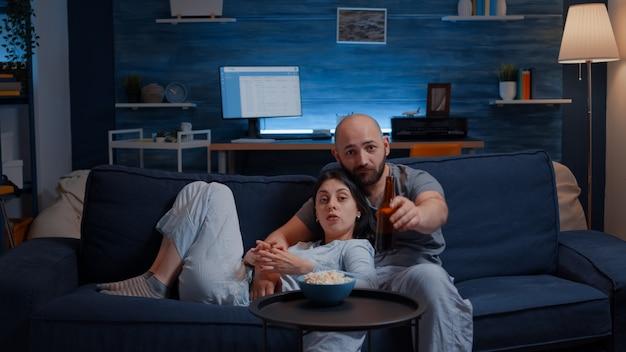 Glückliches paar zu hause, das sich auf dem sofa entspannt und lieblingsfernsehsendungen schaut