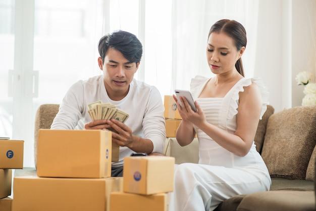 Glückliches paar zu hause im büro mit online-geschäft, online-marketing und freiberuflicher tätigkeit