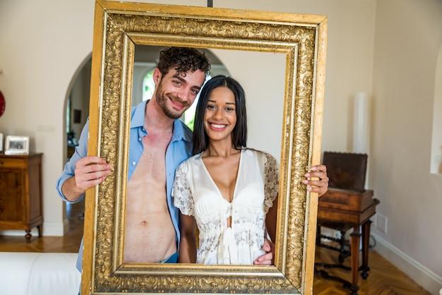Glückliches paarporträt, das einen rahmen hält
