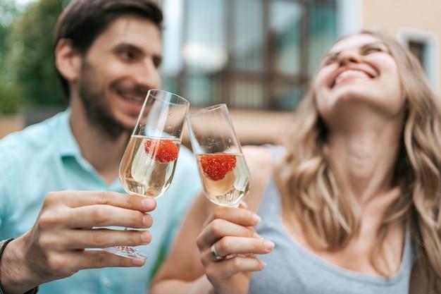 Glückliches paarporträt, das zwei gläser mit sekt und erdbeeren innen mit unscharfem haus auf hintergrund klirrt. liebe feiern