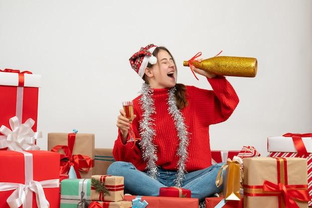 Glückliches partygirl mit der weihnachtsmütze, die champagner trinkt, der um geschenke auf weiß sitzt