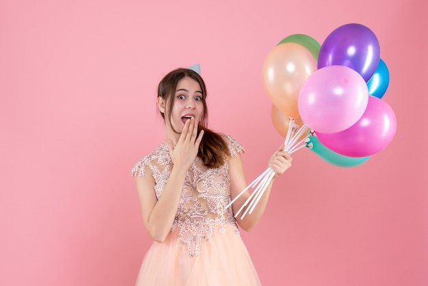 Glückliches partygirl mit partykappe, das luftballons hält, die hand an ihren mund auf rosa setzen