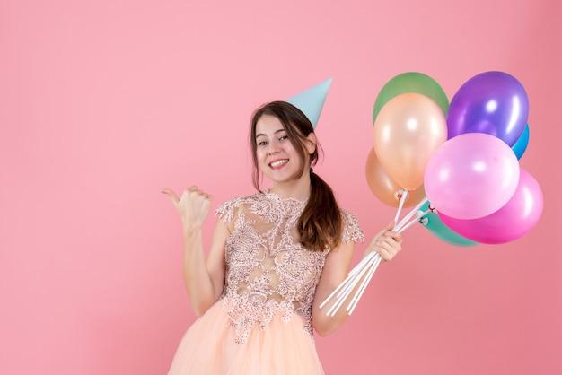 Glückliches partygirl mit partykappe, das luftballons hält, die mit finger etwas auf rosa zeigen