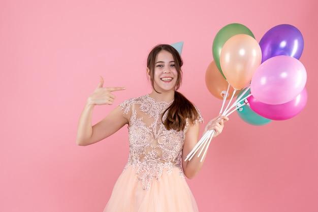 Glückliches partygirl mit partykappe, das luftballons hält, die mit finger selbst auf rosa zeigen