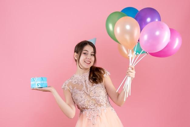 Glückliches partygirl mit partykappe, die bunte luftballons und geschenk auf rosa hält