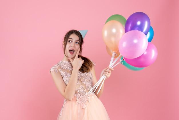 Glückliches partygirl mit partykappe, die luftballons auf rosa hält