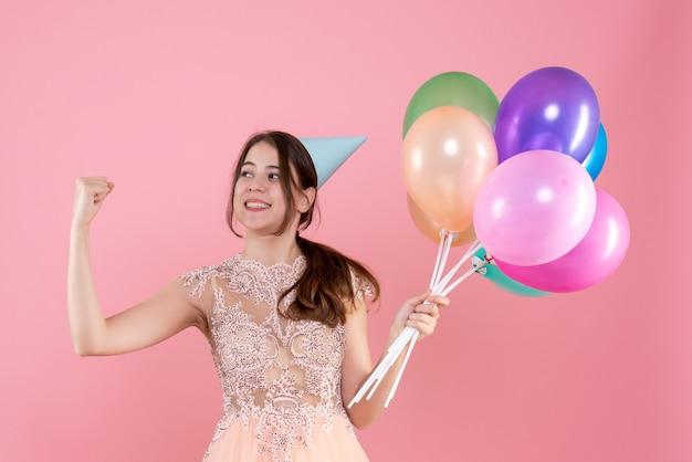 Glückliches partygirl mit partykappe, die luftballons hält, die ihren muskel auf rosa zeigen