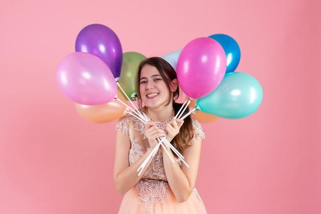 Glückliches partygirl mit partykappe, die luftballons nahe ihrem gesicht auf rosa hält