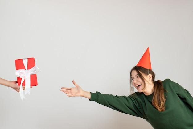 Glückliches partygirl mit partykappe, die versucht, geschenk in menschlicher hand auf weiß zu fangen
