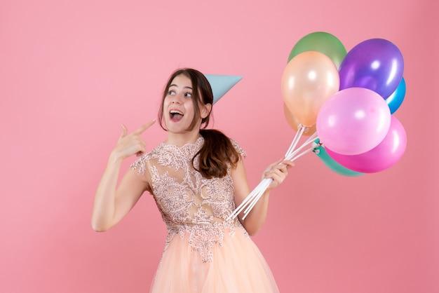 Glückliches partygirl mit partykappe hält luftballons, die mit dem finger ihr lächeln auf rosa zeigen