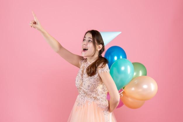 Glückliches partygirl mit partykappe hält luftballons hinter ihrem rücken und zeigt mit dem finger etwas auf pink