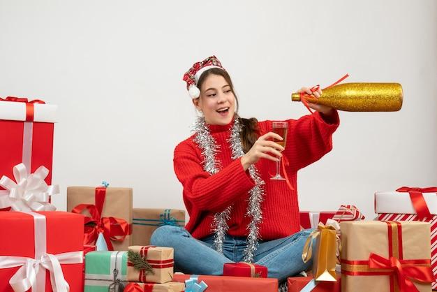Glückliches partygirl mit weihnachtsmütze, die champagner gießt, der um geschenke auf weiß sitzt