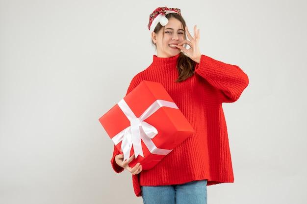 Glückliches partygirl mit weihnachtsmütze, die geschenk auf weiß hält